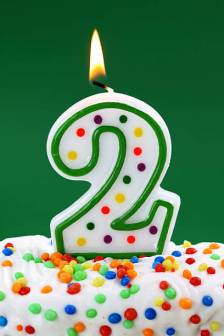 Number two birthday candle on green background